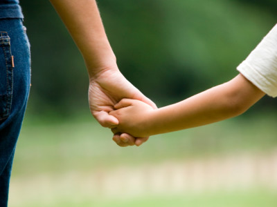 Mothers hand holding kids hand.